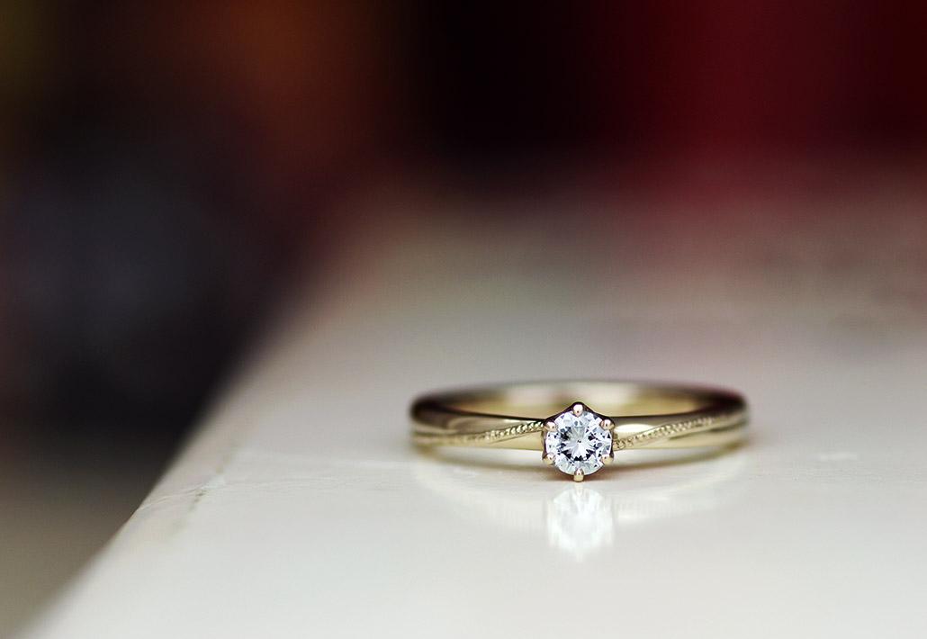 シンプルデザインにミルグレイン加工を施した18金ブラウンゴールドの婚約指輪
