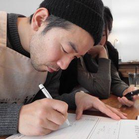 結婚指輪に刻印する文字を描く男性