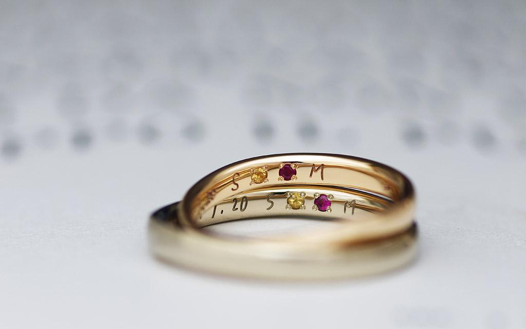直筆文字の刻印とシークレットストーンが入った18金のブラウンゴールドとピンクゴールドの結婚指輪