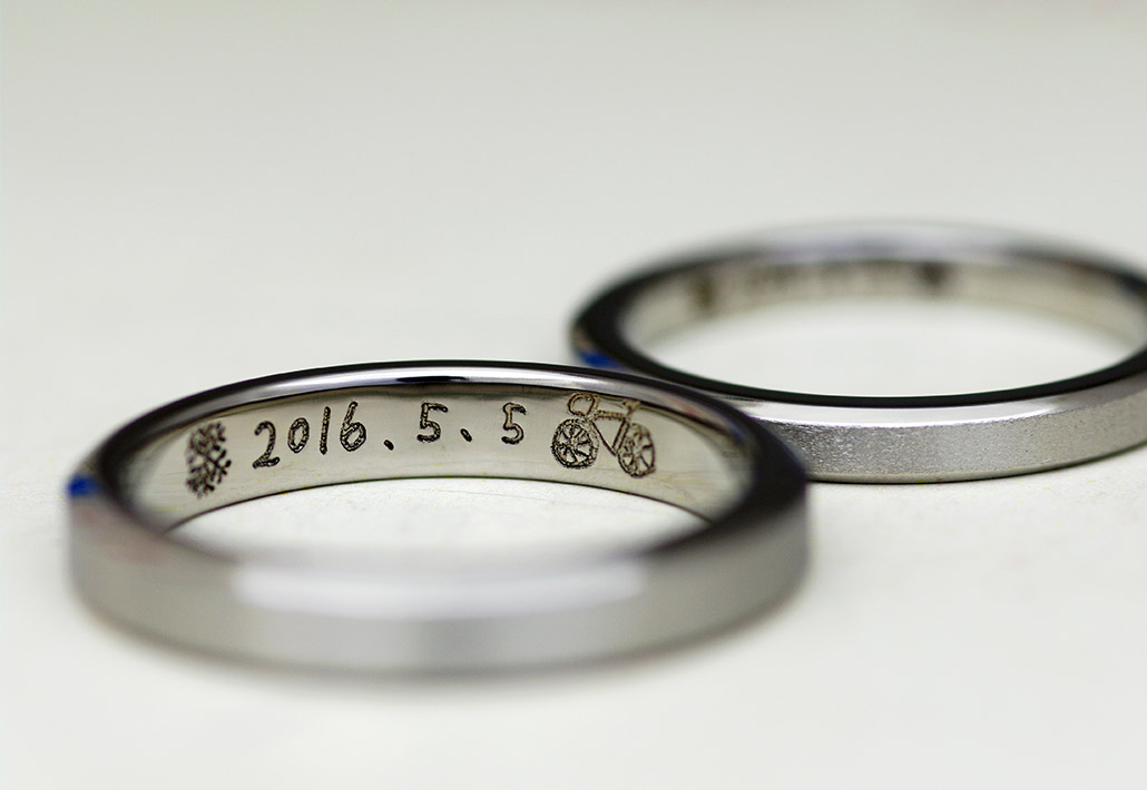 アレルギーフリー素材のチタンで作ったシンプルな平打ちデザインの結婚指輪(マリッジリング)に刻印された手描きの文字とイラスト