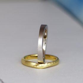 プラチナ素材でアシンメトリーデザインのメンズリングとV字にひねりと鎚目模様を入れたイエローゴールド素材のデザイン違いの結婚指輪(マリッジリング)