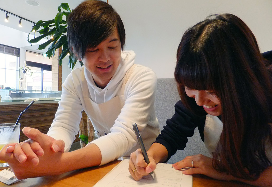 結婚指輪(マリッジリング)の内側に刻印する内容を手書きしているご夫婦