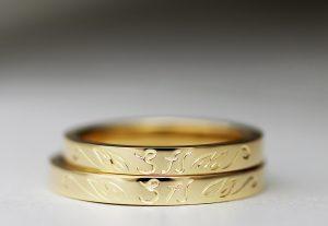 イニシャルデザインの手彫りがお洒落なイエローゴールドのマリッジリング